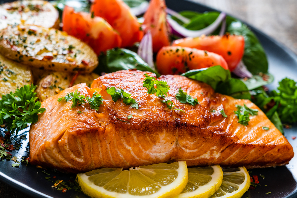 A plate of a salmon dinner. The salmon looks grilled and is sitting on sliced lemon. You can also see a salad and wedge baked potatoes on the plate.