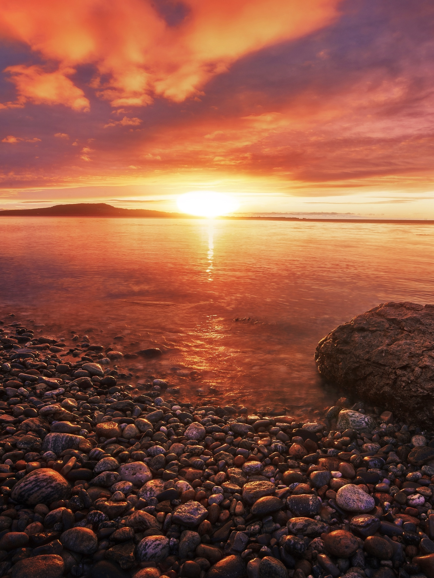 The sun setting on the shores of Shallow Bay in West Newfoundland. The shore is very rocky with large and small rocks. There is a large rock in the water on the shore. The sky is red, orange, and yellow.