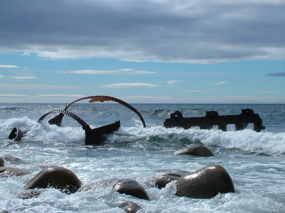 Remains of the SS Ethie shipwreck, one of the best stops on a West Newfoundland itinerary. You can see large rusted pieces of metal in the water with waves crashing against them. There are also large rocks in the water.