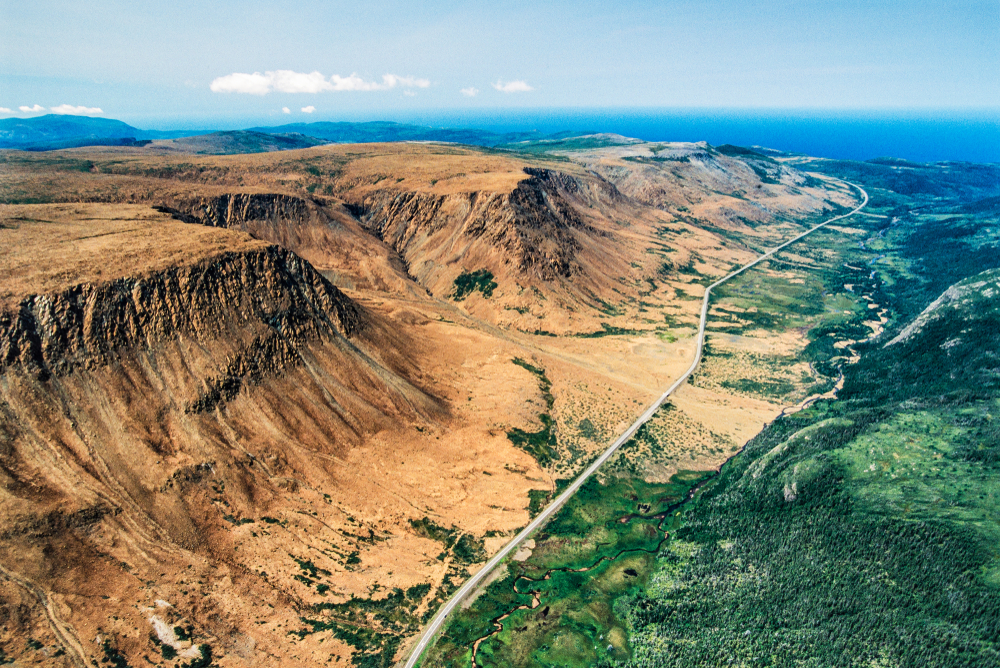 An aerial view of the Tablelands in Gros Morne National Park. It is a sandy looking landscape with large tall plateaus. In the valley there is a boardwalk going straight through it. On the other side of the boardwalk there is a lush green area. It is one of the best things to see on a West Newfoundland itinerary.