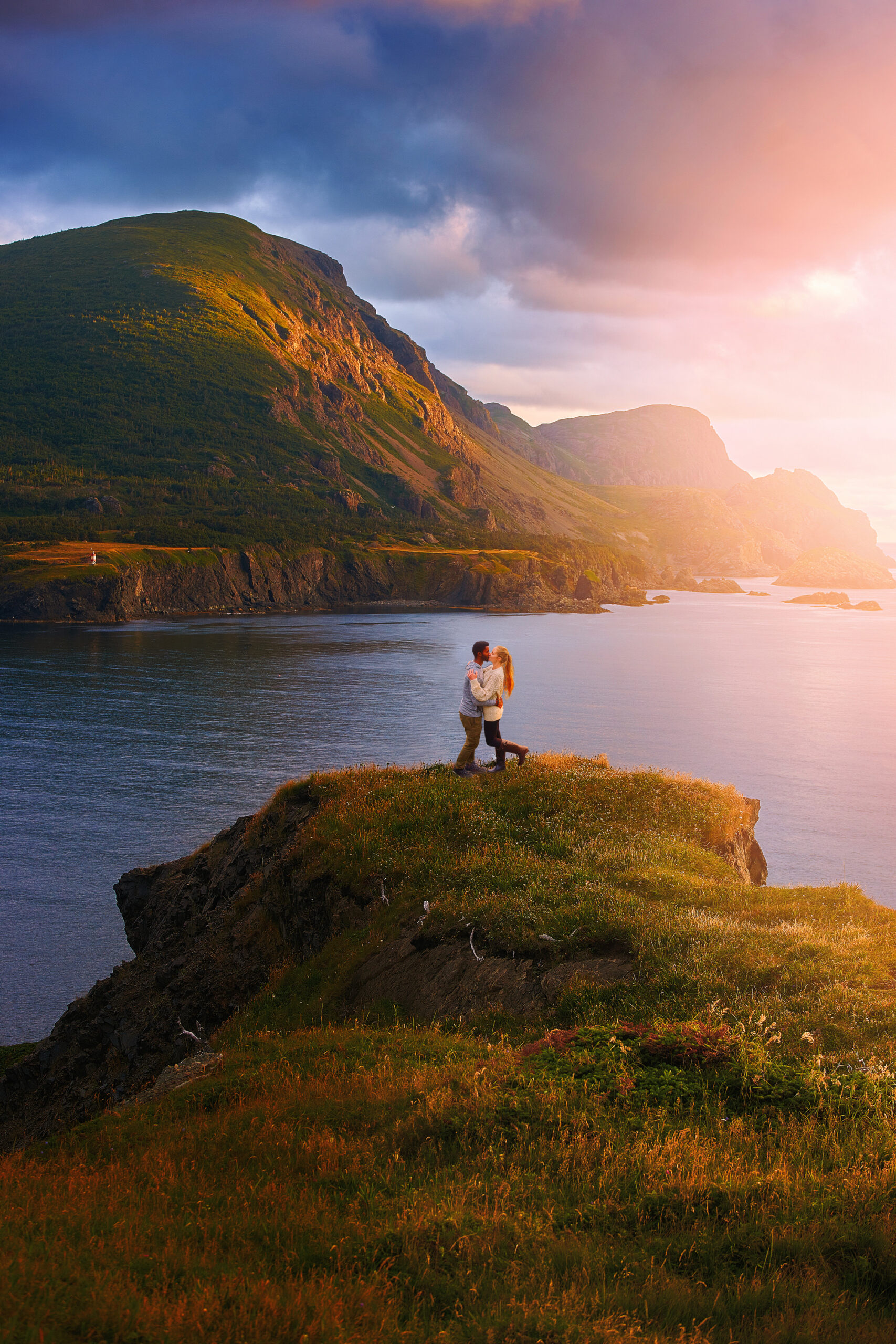A couple kissing on the shore of the Trout River in Gros Morne National Park. There is a mountain range on the other side of the river. The sun is starting to set. It is one of the best stops on a West Newfoundland itinerary.