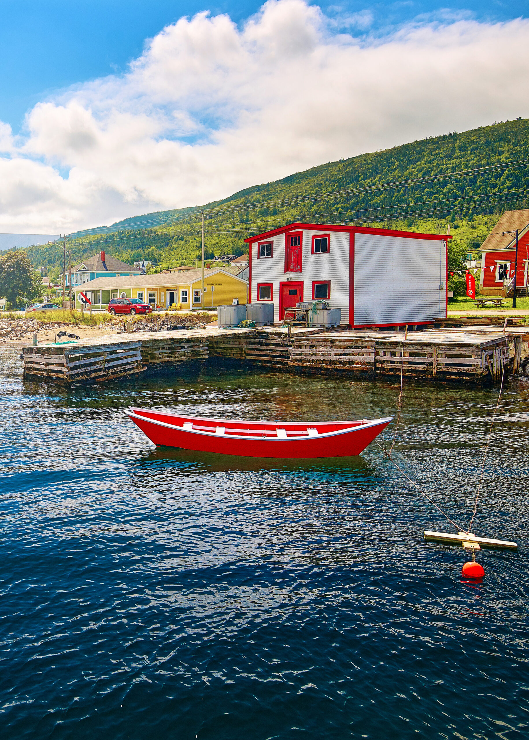 A white and red building on the shore of a bay in Woody Point. There is a red row boat with white trim floating in the water. You can see other colorful buildings that are yellow, blue, and red, in the back ground. There is a hill covered in trees. It is one of the best stops on a West Newfoundland itinerary.