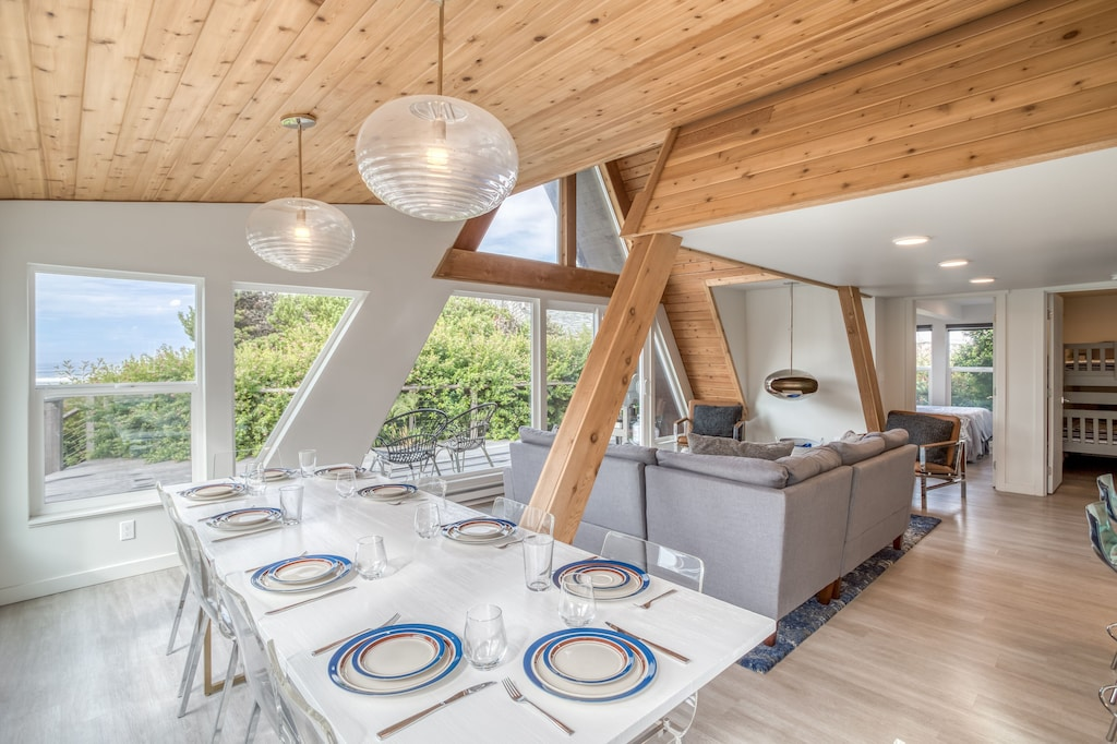 Cool vitage lighting and exposed wood make a statement in the dining area of this retro A frame, one of the best vacation rentals on the Oregon Coast. The table in the photo is set for 10, you could have a great party here!